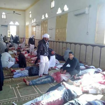 Image: People sit next to bodies of worshippers