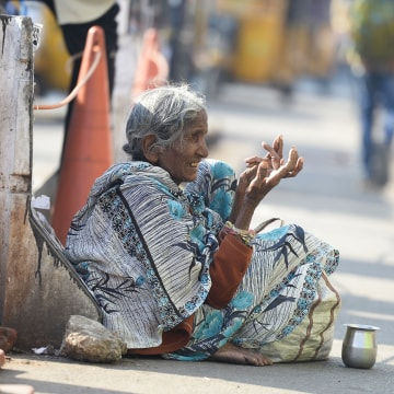 Image: A woman begs on the side of a road in Hyderabad, India