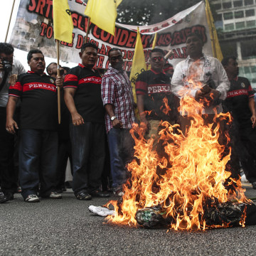 Image: Protesters burn an effigy of Trump in front of the U.S. Embassy in Kuala Lumpur.