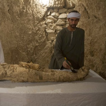 "Image: Egyptian excavation workers restore a mummy in a newly discovered tomb on Luxor's West Bank known as ""KAMPP 150"" during an announcement for the Egyptian Ministry of antiquities about new discoveries in Luxor, Egypt, Dec. 9, 2017."