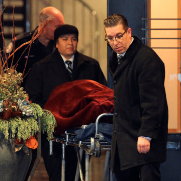 Image: One of two bodies is removed from the Sherman's home in Toronto