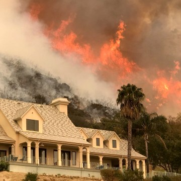 Image: Flames from a back firing operation underway rise behind a home off Ladera Ln near Bella Vista Drive in Santa Barbara, California on Dec. 14, 2017.