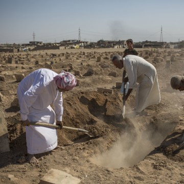 Image: Family members bury their relative in a graveyard in Mosul after his body was exhumed
