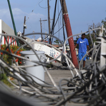 Image: A man walks past downed electricity poles in the Punta Santiago beachfront neighborhood in Humacao