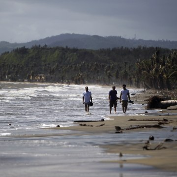 Image: Tourists wade in the water along the beach in the Punta Santiago beachfront neighborhood in Humacao