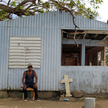 Image: Jose Luis Lluveras, 74, sits in front of his home that was destroyed during Hurricane Maria