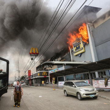 Image: A firefighter stands in front of a burning shopping mall in Davao City