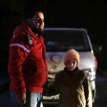 Image: A member of the Syrian Arab Red Crescent stands with a girl during a human evacuation of sick people from eastern Ghouta