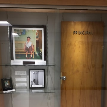 Image: A display case with photos, an illustration and the door that was once on the Principal's office at Cambridge Central Schools in Cambridge