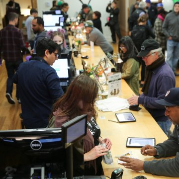 Image: Customers purchase marijuana at a dispensary in Oakland on the first day of legalized recreational marijuana sales in California