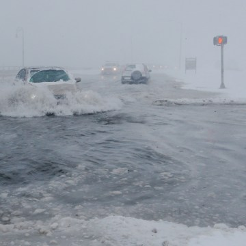 Image: Drivers make their way along the flooded Beach Road after the ocean overtopped the seawall in the Boston suburb of Lynn