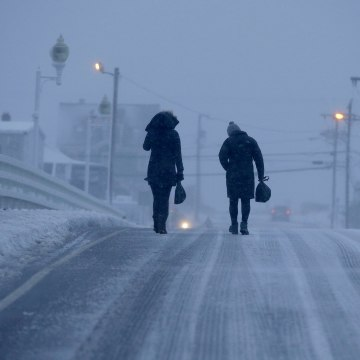 Image: Two people walk across the Humarock bridge as blizzard conditions begin to wind-down on Jan. 4, 2018, in Marshfield, Massachusetts.
