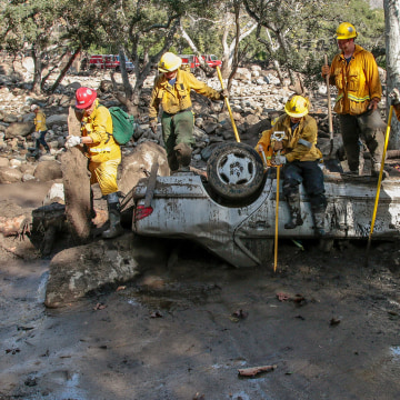 Image: Rescue workers search cars for missing persons after a mudslide in Montecito, California,