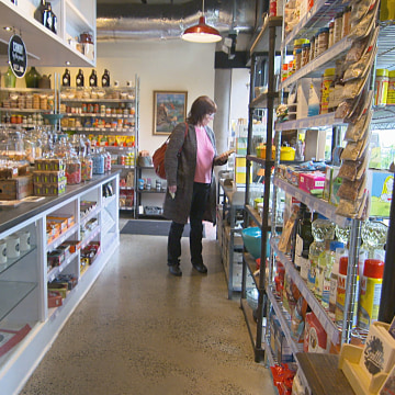 Woman shops at Cone and Steiner in Seattle, Wa. that specializes in local goods and is a business creating jobs.