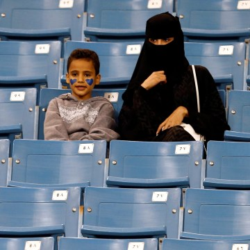 Image: A Saudi woman watches soccer