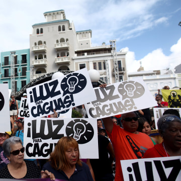 Image: People hold signs during a protest demanding that authorities fix the electrical grid which was mostly destroyed after Hurricanes Irma and Maria hit the island in September, in San Juan