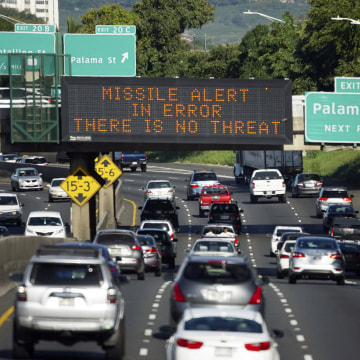 """Image: Cars drive past a highway sign that reads """"MISSILE ALERT ERROR THERE IS NO THREAT"""""""