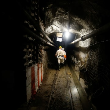 Mine security officials walk underground at Sibanye Gold's Masimthembe mine in Westonaria
