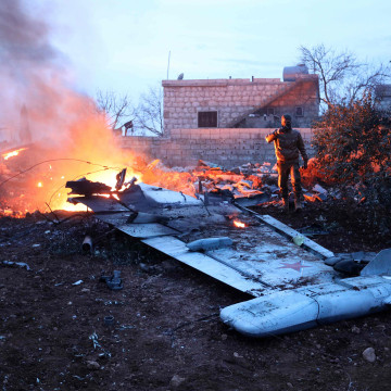 Image: A rebel fighter takes a picture of a downed fighter jet