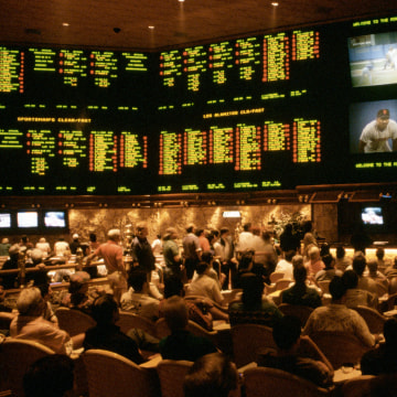 Image: Gamblers bet on a variety of sporting events in the Sports Book, the betting lounge at the Mirage casino.
