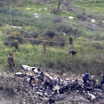 Image: Israeli soldiers inspect the remains of an Israeli F-16 fighter jet that was shot down after a hit by Syrian anti-aircraft system, near the northern Israeli Kibbutz (collective community) of Harduf, on Feb. 10, 2018.