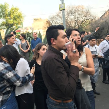 Image: People stand on the street after an earthquake shook buildings in Mexico City
