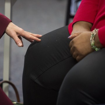 Image: Tara Bassett, development specialist, touches Kimberly Singleton knee for support during a presentation at Bridgehaven Mental Health Services.