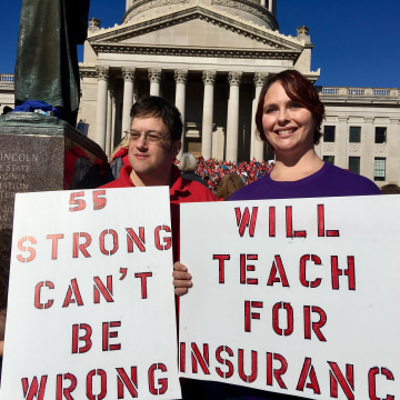 "Image: Teacher John and Kerry Guerini of Fayetteville, West Virginia, hold signs ""title ="" Image: Teacher John and Kerry Guerini of Fayetteville, West Virginia, hold signs ""/> </noscript><br /> <a href="