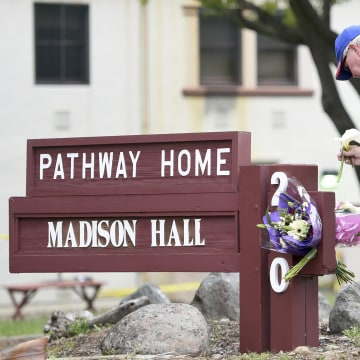 Image: Resident Tom Parkinson places flowers on a sign at the Veterans Home of California, the morning after a hostage situation in Yountville, California, on March 10, 2018.