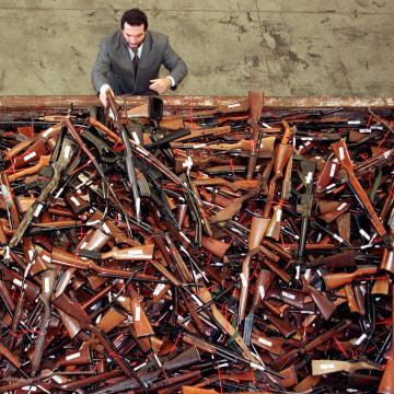 Image: Mick Roelandts, firearms reform project manager for the New South Wales Police, looks at a pile of about 4,500 prohibited firearms