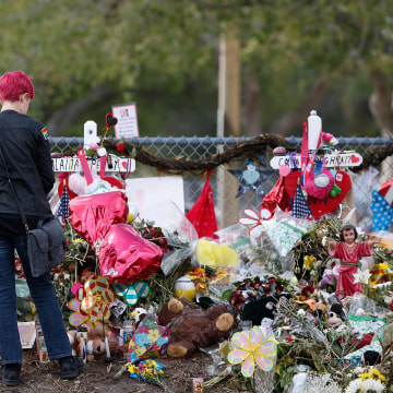 Image: A Marjory Stoneman Douglas High School student stops to look at one of the memorials