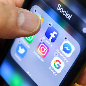 Image: A man holds a smart phone with the icons for the social networking apps Facebook, Instagram and Twitter seen on the screen