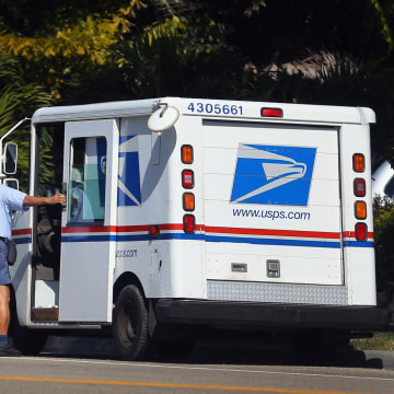 In this file photo, a mailman for the U.S. Postal Service closes the door on his postal vehicle on November 15, 2012 in Miami, Florida.