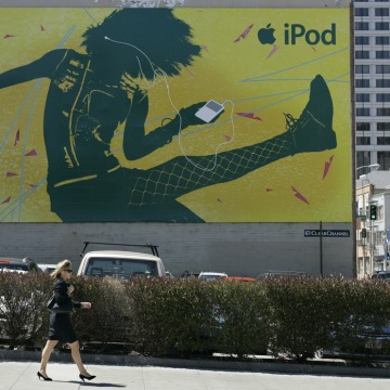 A woman listens to her portable music player while walking past an Apple Ipod billboard in San Francisco, Monday, April 23, 2007. Apple Inc., on a tea...