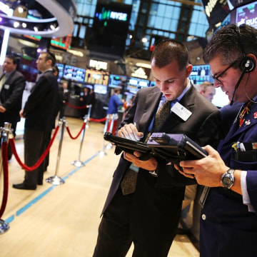 Traders work on the floor of the New York Stock Exchange at the end of the trading day on August 1, 2013 in New York City.