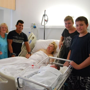 Mother Maxime Marin is surrounded by family members after giving birth to Maria Lorena Marin