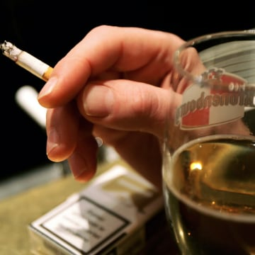 PARIS - JANUARY 31:  A man smokes a cigarette in a bar on January 31, 2007 in Paris, France. France will introduce a smoking ban in public places Febr...