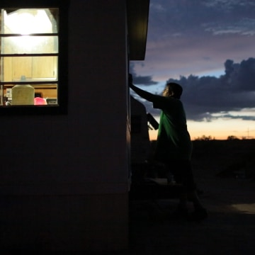 A young man stands outside of a trailer on the Navajo reservation. Earlier in the day, the home was wired with solar power and LED lights. Wednesday, ...