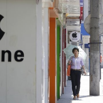 A woman walks past a logo of Apple Inc in Wuhan, Hubei province July 24, 2013. REUTERS/Darley Shen