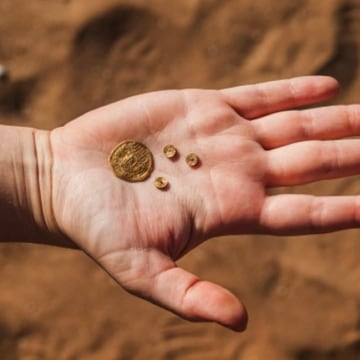 Inside of an ancient garbage pit, archaeologists discovered precious artifacts, including a gold coin and three items inlaid with gold that adorned jewelry.