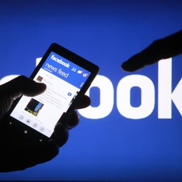 A smartphone user shows the Facebook application on his phone in the central Bosnian town of Zenica, in this photo illustration, May 2, 2013. REUTERS/...