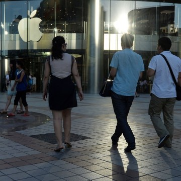 Shoppers walk outside an Apple store at the Wangfujing shopping street in Beijing on July 24, 2013.  Apple said its revenue from China fell 14 percent...