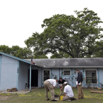 Engineers work in front of a home where sinkhole opened up underneath a bedroom and swallowed a man on March 1 in Seffner, Fla.
