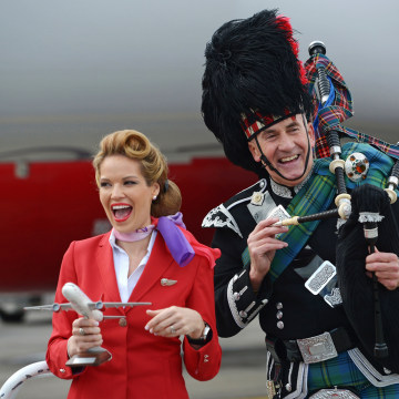 EDINBURGH, SCOTLAND - APRIL 08:  An air hostess reacts with a piper as Sir Richard Branson arrives in Edinburgh Airport wearing a Harris Tweed Kilt on...