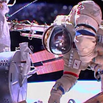Russian cosmonaut Fyodor Yurchikhin works outside the International Space Station, with the Earth far below, in this still from a NASA broadcast on Aug. 16, 2013.