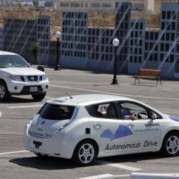 A prototype Nissan Leaf autonomous vehicle  negotiates a simulated urban intersection, complete with cross traffic.