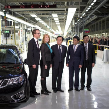 From left to right, NEVS MD Mattias Bergman, Swedish Minister for Enterprise Annie Loof, Chinese Ambassador Chen Yuming, vice mayor of Qingdao Li Chenggang and State Power Group CEO Kai Johan Jiang stand next to a first production NEVS Saab 9-3 Aero at the Trollhattan factory in Sweden on Dec. 2. The new owners of Swedish car maker Saab, National Electric Vehicle Sweden AB, restarted production of the 9-3 sedan Monday.