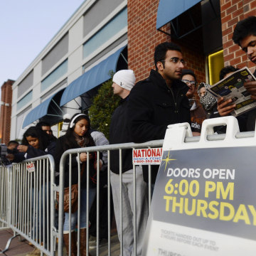 People look at a listing of sale-items while waiting in a line for a Best Buy to open on Thanksgiving Day in Alexandria, Va. An earlier start to the traditional holiday shopping weekend put a dent in sales.