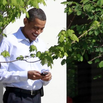 President Barack Obama uses his BlackBerry e-mail device as he walks at Sidwell Friends school where their daughter Sasha attends in Bethesda, Md., Th...