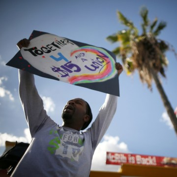 Joe Ben Johnson III holds a sign outside McDonald's in Los Angeles, California, December 5, 2013. Organizers say fast food workers will strike in 100 ...